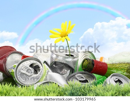 Garbage with growing daisy under rainbow - stock photo