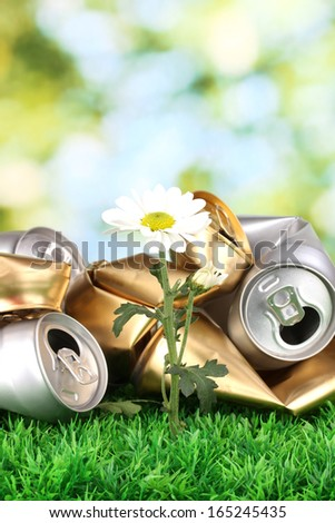 Garbage with growing flower. Environmental conservation concept - stock photo