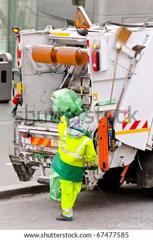 Garbage worker with bag at dump truck - stock photo