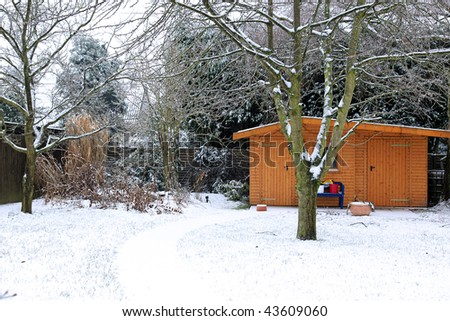 garden and summerhouse in wintertime during snowfall - stock photo