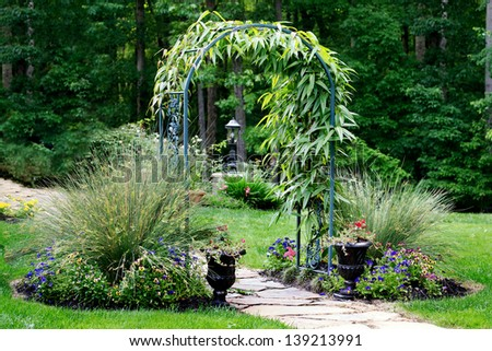 Garden arbor leading to forest path - stock photo