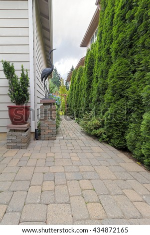 Garden Backyard Patio and Brick Paver Path with Potted Plant Decor Column and Evergreen Trees Landscaping - stock photo
