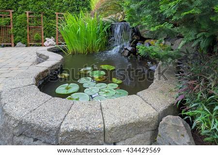 Garden Backyard pond with waterfall water plants brick paver patio trellis landscaping - stock photo