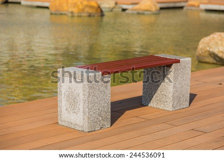 Garden bench beside the pond, the bench made of granite legs with Chinese style carving - stock photo