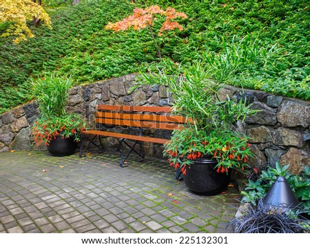 Garden bench in the fall surrounded by lush vegetation - stock photo