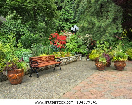 Garden bench surrounded by lush spring vegetation - stock photo