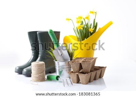 garden boots, watering can and garden tools isolated on white - stock photo