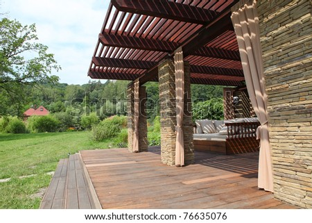 Garden brick house with wooden couch and white pillows - stock photo