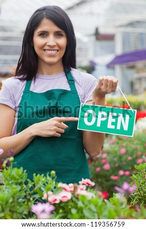 garden center employee holding an open sign and pointing on it - stock photo