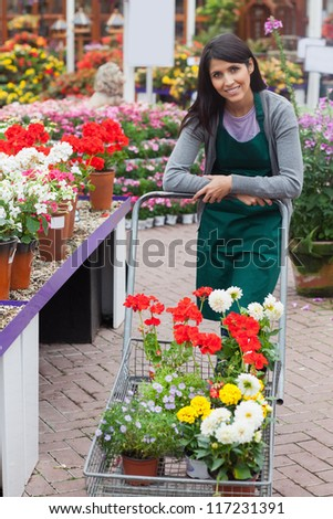 Garden center employee pushing trolley filled with plants - stock photo