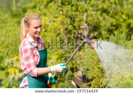Garden center woman worker watering plants with hose smiling sunny - stock photo