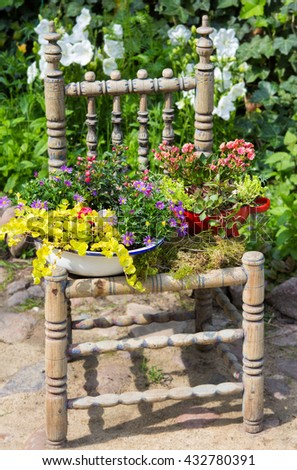 Garden decoration with a old chair and different plants makes a unique eyecatcher. - stock photo