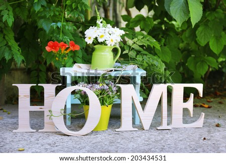 Garden decoration with wildflowers and decorative letters, outdoors - stock photo