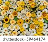 Garden fence made of different artificial flowers - stock photo
