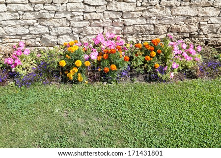 Garden flowers bed next to limestone rocks and green grass - stock photo