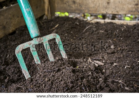 Garden fork turning black composted soil in wooden compost bin - stock photo