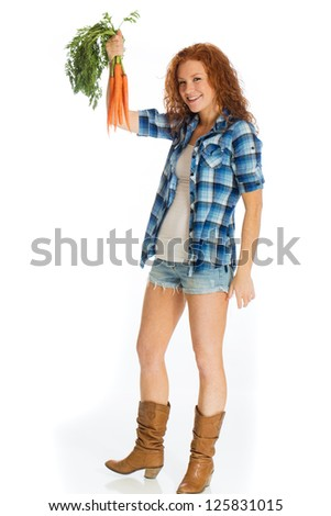 Garden fresh carrots being held by a beautiful, country girl with cowboy boots. - stock photo