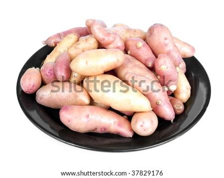 Garden fresh rose fingerling potatoes on black plate isolated on white - stock photo