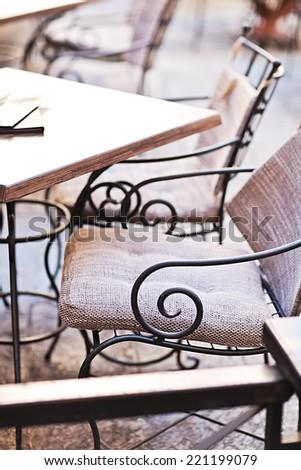 garden furniture on italian narrow street in small town - stock photo