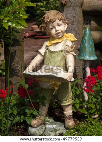 Garden gnome dwarf statue of a boy made from wood - stock photo