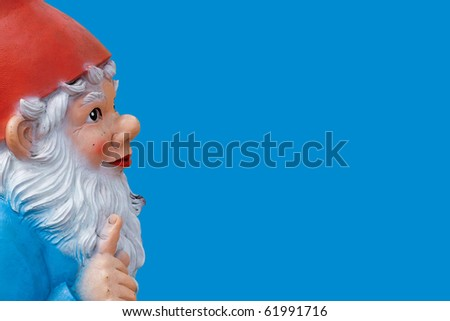 garden gnome with a wagging finger isolated on blue - stock photo