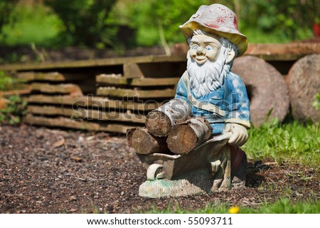 Garden gnome with barrow full of firewood - stock photo