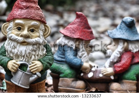 Garden gnomes at work and play - stock photo