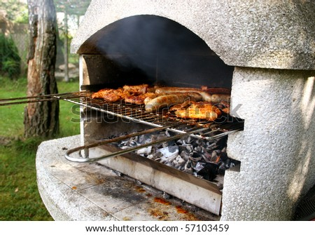 Garden grill with steaks and german Bratwurst - stock photo