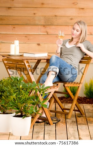 Garden happy woman enjoy glass wine sitting on terrace