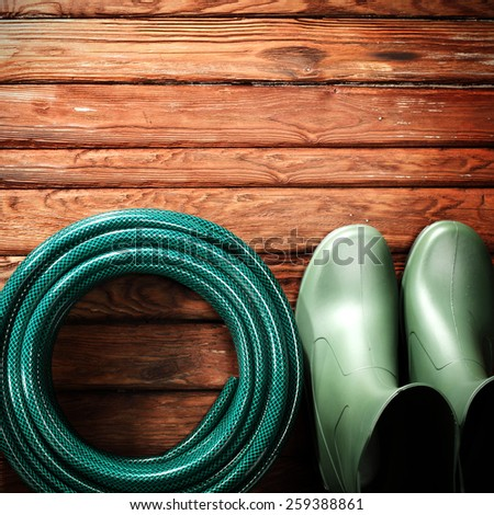 garden hose and shoes  - stock photo