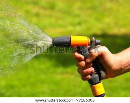 Garden hose. Green grass background. - stock photo