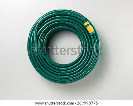 Garden Hose Isolated on a White Background with Soft Shadow. Top View of a Classic Green Rubber Hose with Copy Space for Text or Image.  - stock photo