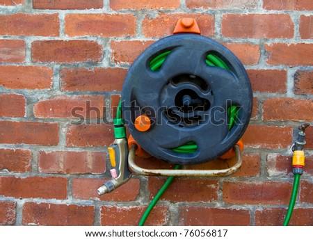 Garden hosepipe on the wall - stock photo