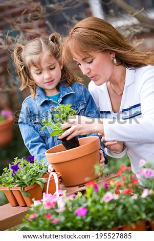 Garden: Mother And Daughter Potting Flowers