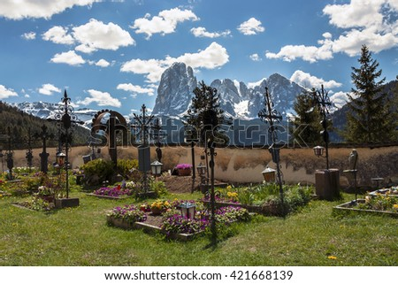 Garden of San Giacomo church with beautiful graves before a big mountain