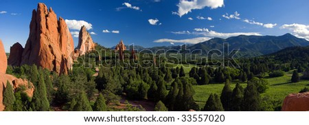 Garden of the Gods Panorama at it's Best! Two people taking a sidewalk stroll through the Massive Garden of the Gods Park, dwarfed by the size of the Grand Scale of it's Beauty. - stock photo