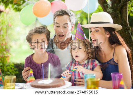 Garden party for daughter's birthday with mum and dad, the whole family helping to blow her candles, the garden is decorated with balloons and colors are bright - stock photo