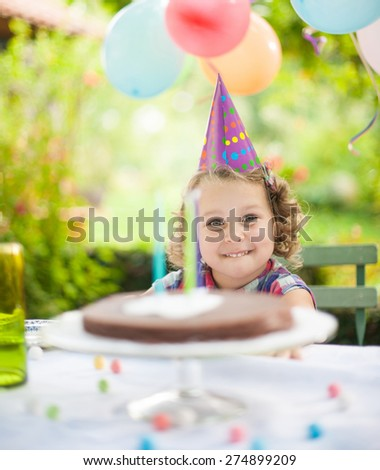 Garden party for the birthday girl. Smiling kid facing her cake at the table - stock photo