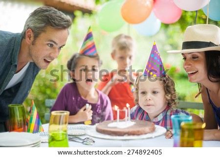 garden party with family for little girl's birthday, kid makes a wish and blows out the candles, the garden is decorated with balloons and colors are bright