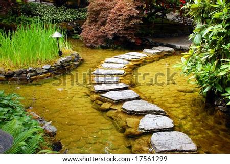 Garden path across pond - stock photo
