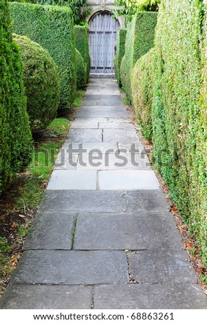 Garden Pathway Lined with Topiary Hedge - stock photo
