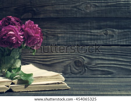 Garden pink roses and old books on a wooden surface