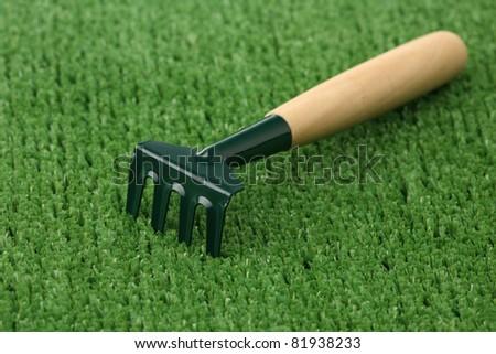 Garden rake on a green background of artificial grass - stock photo