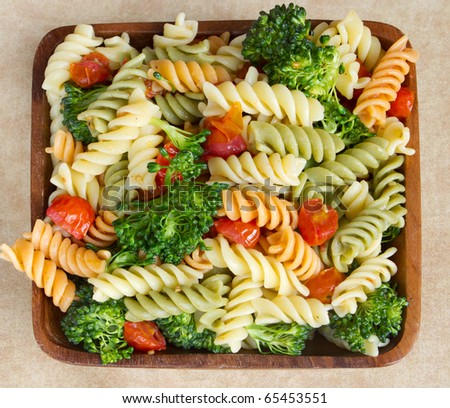 garden rotini salad with broccoli and tomatos closeup in a wooden bowl - stock photo
