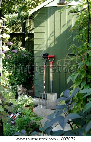 Garden Shed and gardening Tools with a cat in the background - stock photo