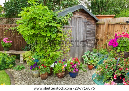 Garden shed surrounded by colorful potted plants and shrubs. - stock photo