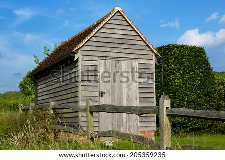 Garden Shed. Traditional lap wood shed found in many gardens. Set in the corner of a garden on a summers day. - stock photo