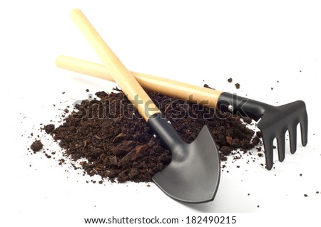 garden spade and a rake on peat soil separately on a white background
