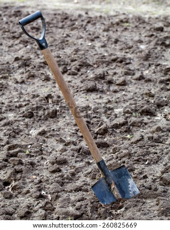 Garden spade stacked in ploughed ground - stock photo