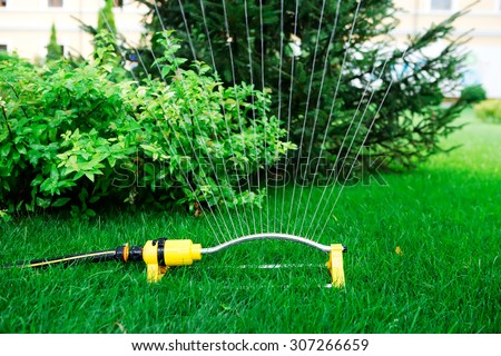 garden sprinkler system irrigates water jets grass and trees - stock photo
